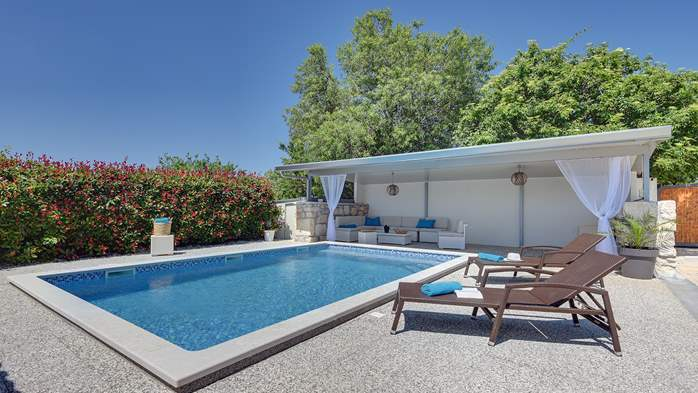 Villa with pool and outdoor kitchen surrounded by greenery, 2